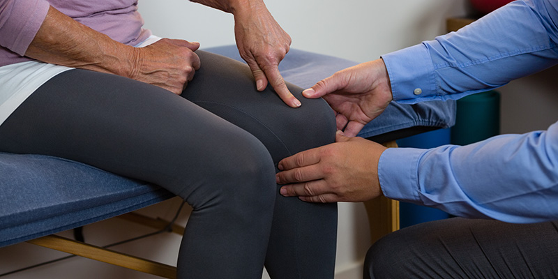 physiotherapist examining a female patients knee. buy cbd topicals online usa.
