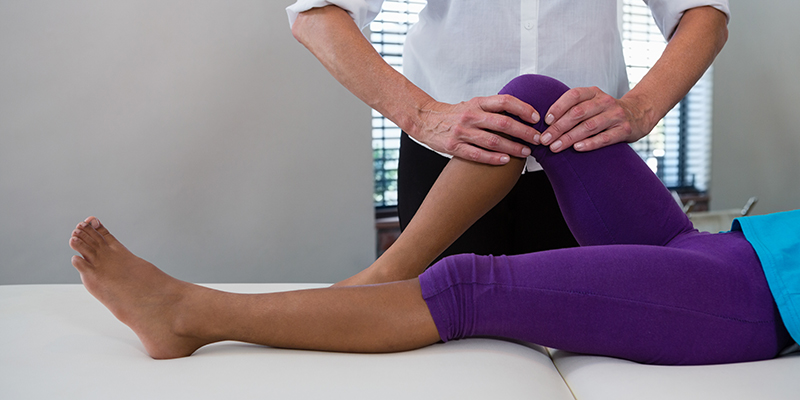 physiotherapist giving leg massage to a woman. CBD rub for joint pain.